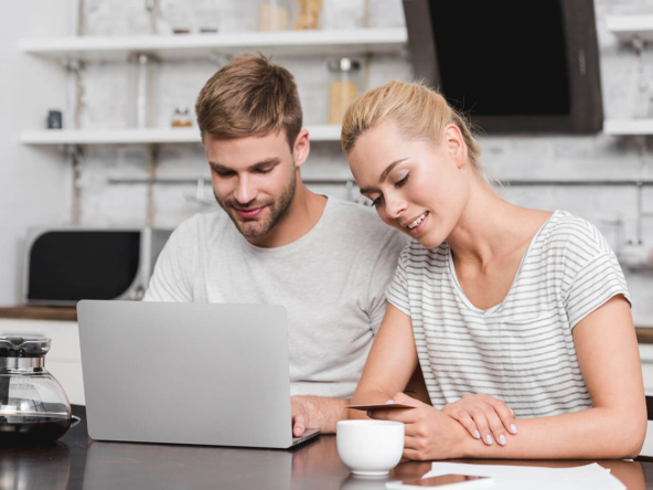 couple sitting by laptop choosing lease grand cayman