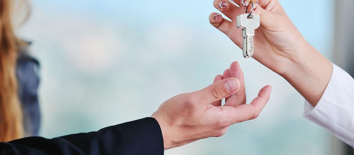 man handing over apartment keys in grand cayman